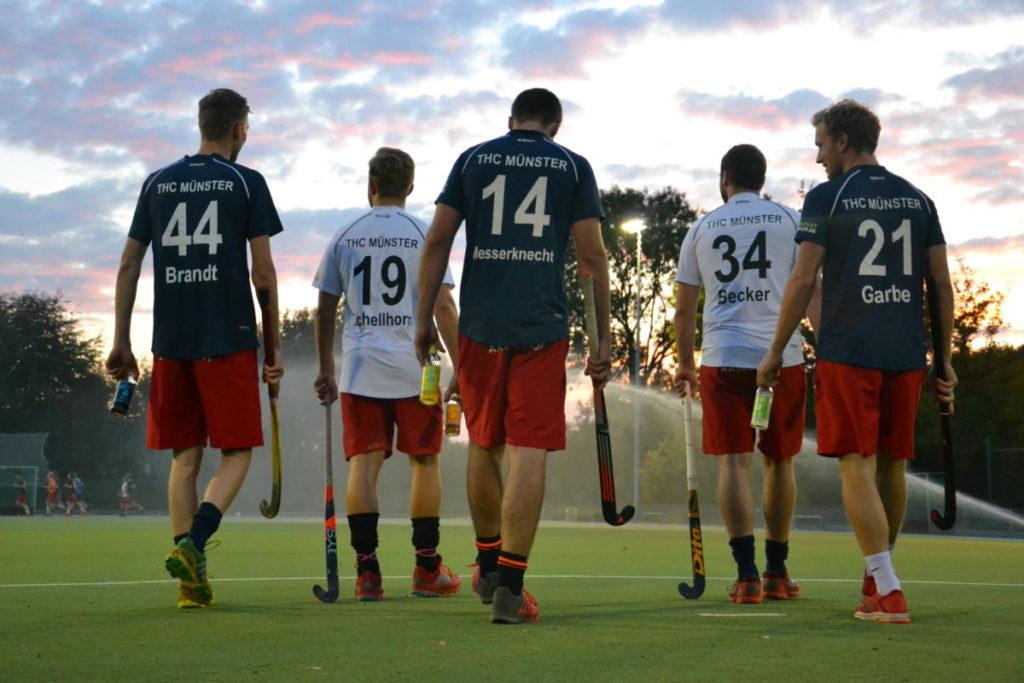 Spieler vom THC Münster gehen dem Sonnenuntergang mit einer liba in der Hand entgegen